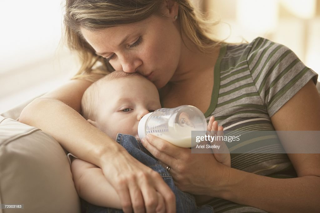 Mother feeding baby with bottle on sofa