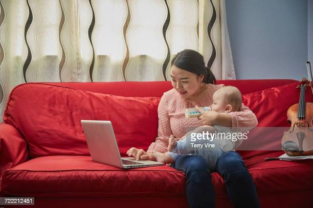 Mother feeding bottle to baby son on sofa and using laptop