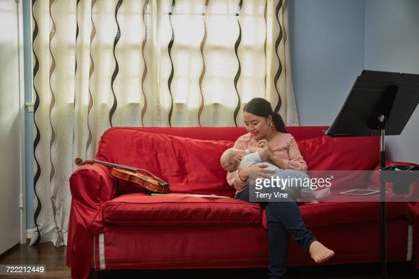 Mother feeding bottle to baby son on sofa