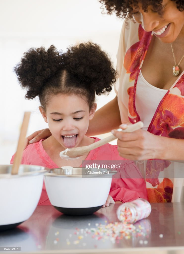 Mother feeding daughter from mixing bowl : Stock Photo