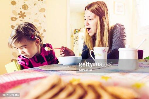 Mother feeding fussy daughter breakfast