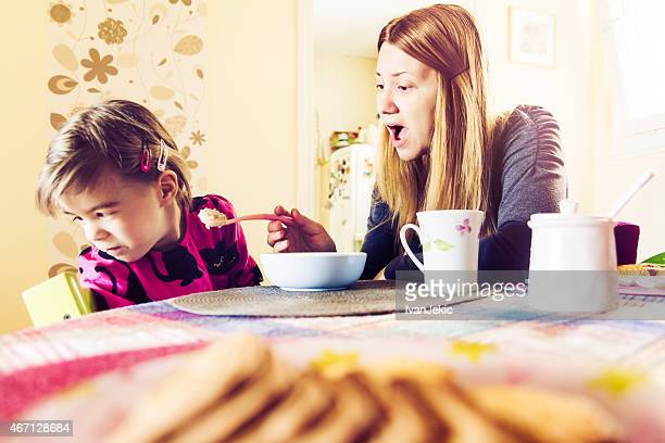 Mother feeding fussy daughter breakfast