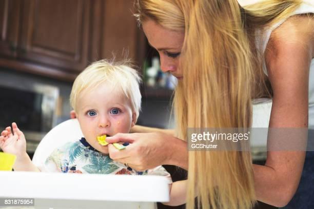Mother feeding her child breakfast