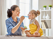 Happy young mother feeding her baby girl with a spoon at home.