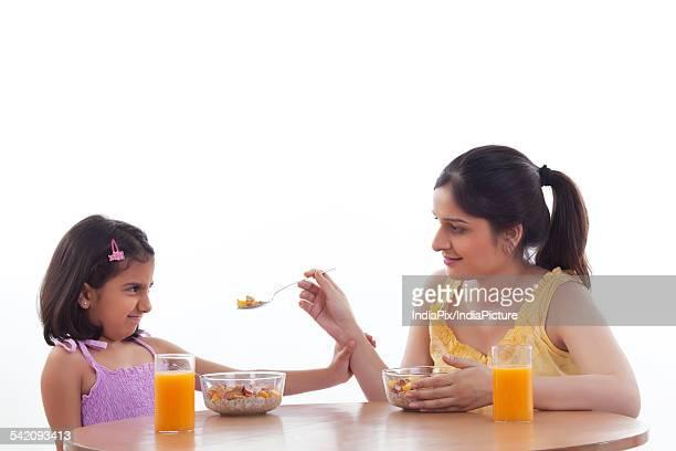 Mother feeding her daughter breakfast
