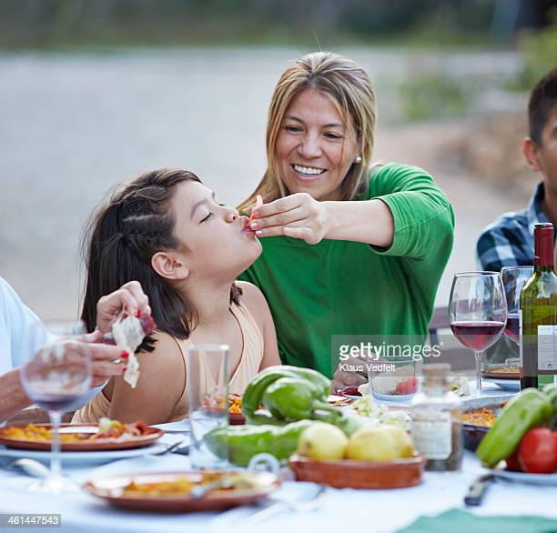 Mother feeding her daughter with tomato at dinner