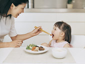 Mother Feeding Her Young Daughter Japanese Food With Chopsticks at the Dining Room Table