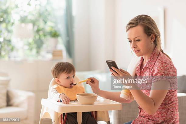 Mother feeding little boy (2-3 years) in high chair and texting message