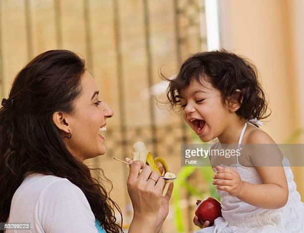 Mother Feeding Little Girl