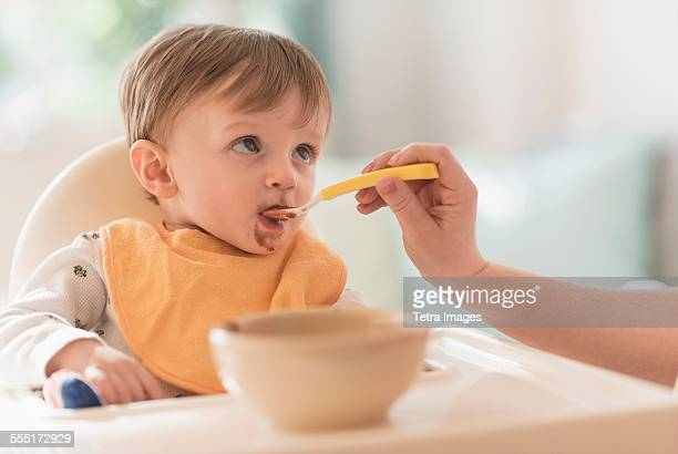 Mother feeding small boy (2-3) with spoon