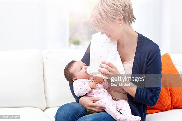 Mother feeding to little girl with baby bottle