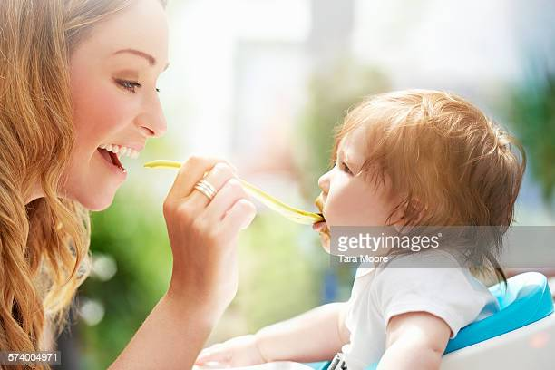 Mother feeding toddler at home