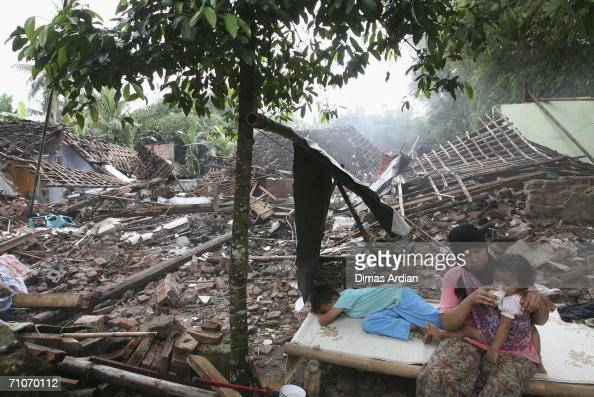 A mother feeds her baby in front of rubble of her wrecked house in devastated Bantul regency May 28 2006 in Yogyakarta Central Java Indonesia A...