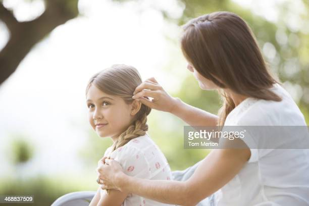 Madre figlia di correzione dei capelli all'aperto