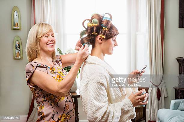 Mother fixing hair while daughter is texting.