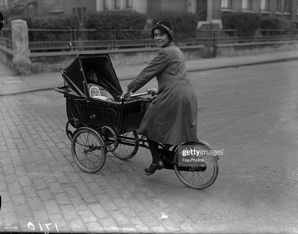 A mother gets all the exercise she needs pushing her pram and cycling at the same time and the baby gets a taste for speed at an early age