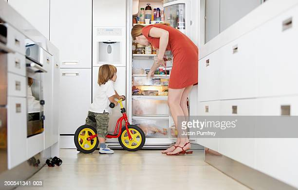 Mother getting food from fridge with son (2-4) on bicycle