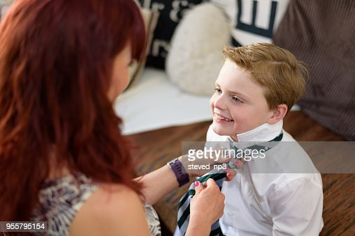 Mother getting son dressed for school at home : Stock Photo