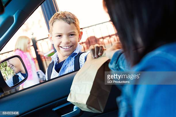 Mother gives son his lunch in carpool line at school