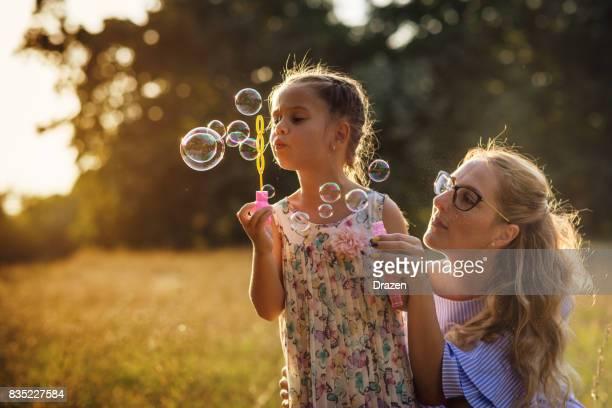 Mère donne appui à sa petite fille tout en soufflant des bulles