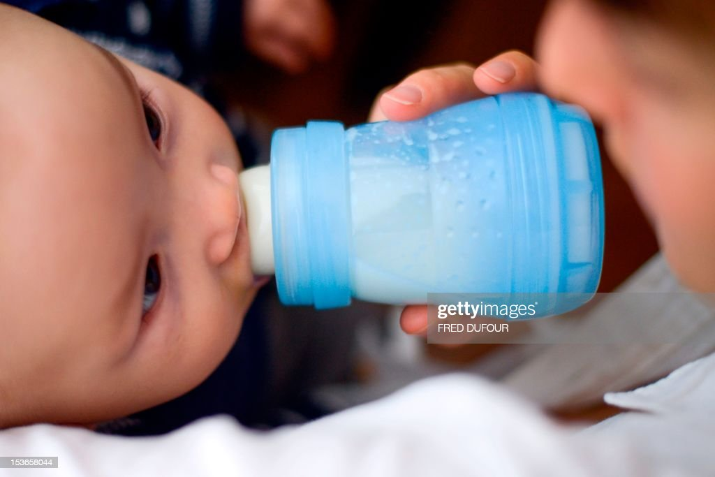 A mother gives the bottle to her baby on October 8, 2012 in Paris. One year after the National Assembly, the French senate will exam on October 9, 2012, a socialist proposal for a law prohibiding the bisphenol-A used in the food packagings. AFP PHOTO / FRED DUFOUR