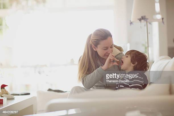 Mother giving a piece of chocolate to her son