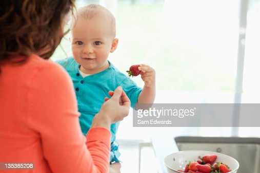 Mother giving baby strawberry : Stock Photo