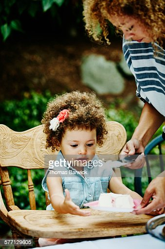 Mother giving cake to daughter at party