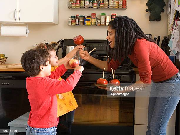 Mother giving caramel apples to kids