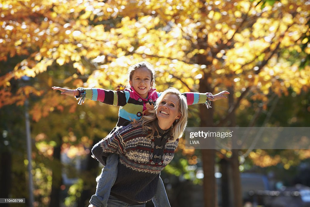 Mother Giving Daughter A Piggyback Ride, Outdoors : Stock Photo