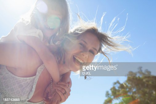 Mother giving daughter piggy back