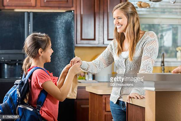 Mother giving daughter sack lunch before leaving for school
