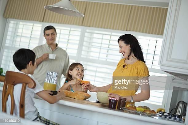 Madre dando a su hija en la cocina con frutas