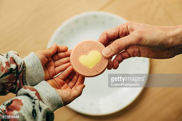 A mother giving heart cookie to her child