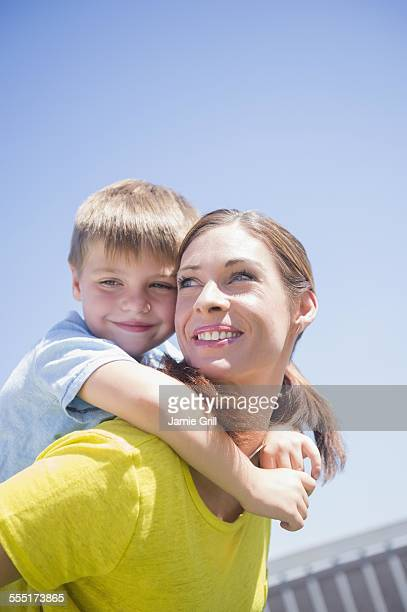 Mother giving her son (6-7) piggyback ride