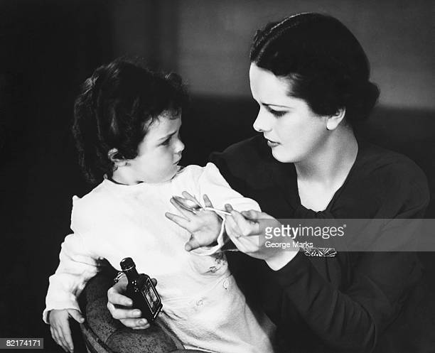 Mother giving medicine to baby girl (12-15 months), (B&W)