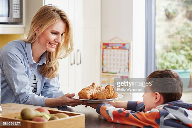 Mother giving son croissant