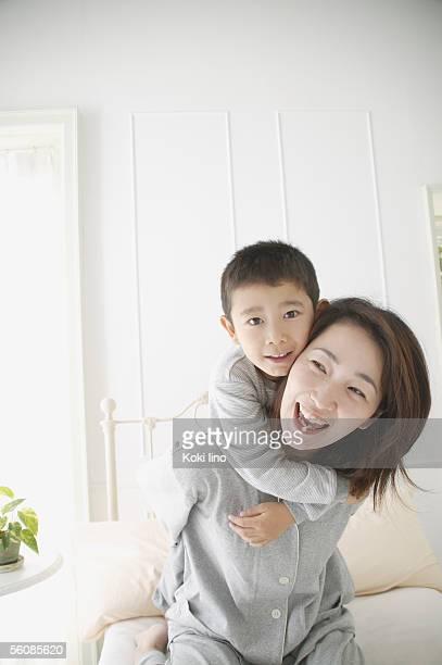 Mother giving son piggyback