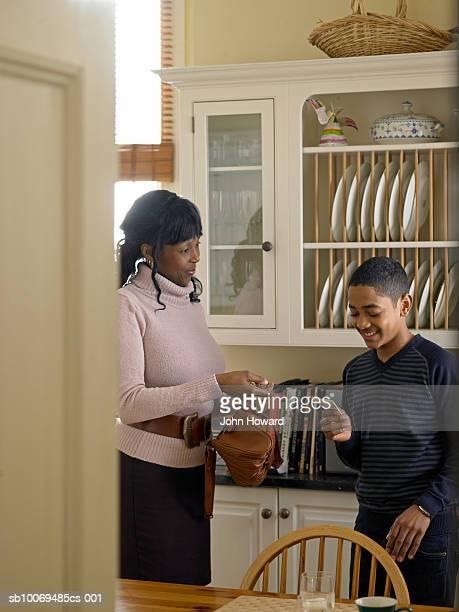 Mutter gibt Sohn (12-13) Taschengeld in der Küche