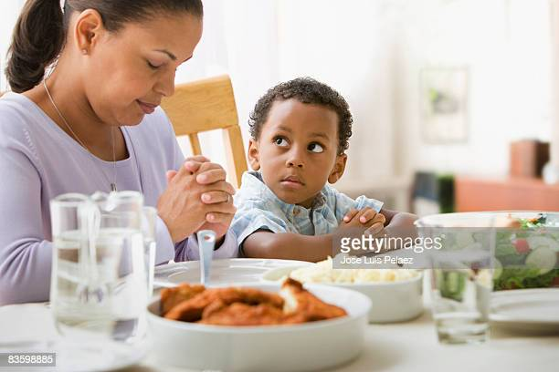 Mother giving thanks at the dinner table with son