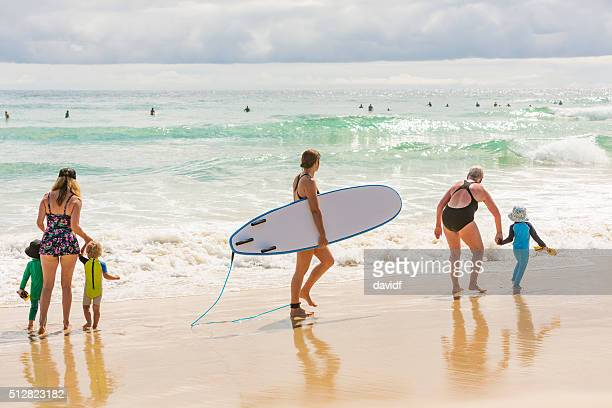 Mother, Grandmother and Children at the Beach With Female Surfer