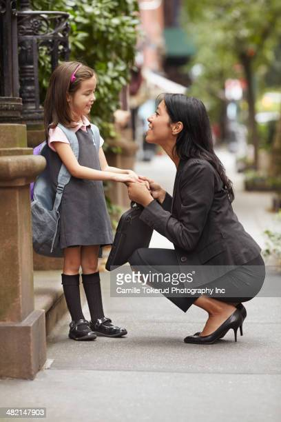 Mother greeting daughter on city street