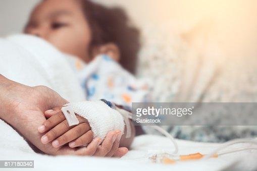 Mano mano de niño con solución intravenosa en el hospital con amor y cuidado de la madre : Foto de stock