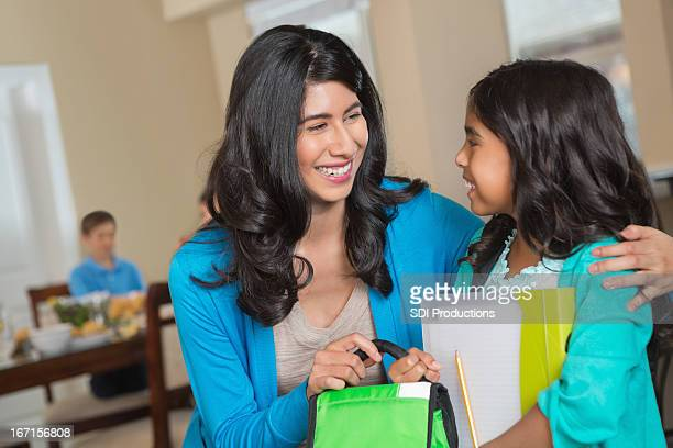 Mother handing daughter  lunch bag as she leaves for school