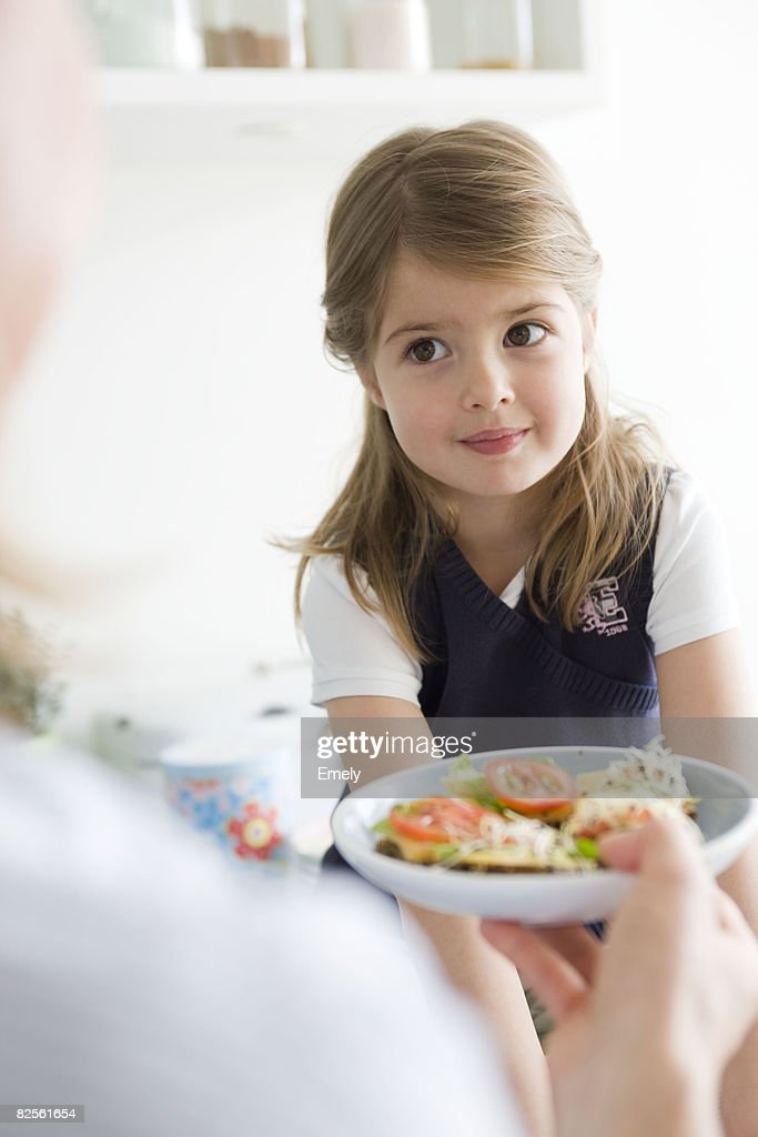 Mother handing plate to daughter