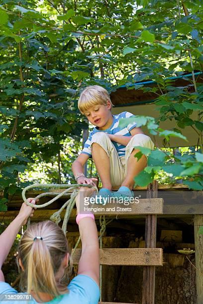 Mère tendre la corde à son fils en treehouse