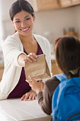 Mother handing sack lunch to daughter