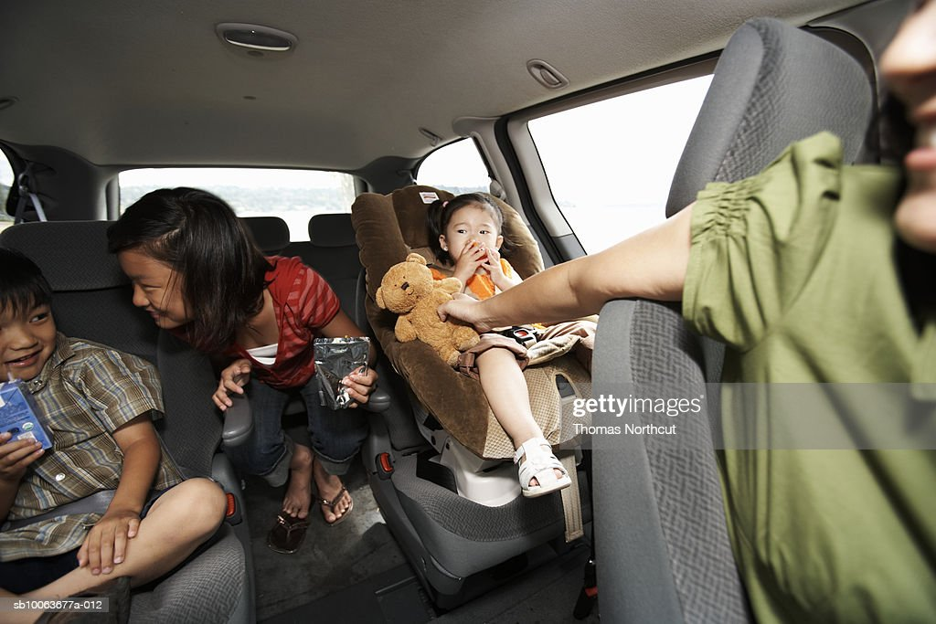 Mother handing toy to children (1-10) travelling in car : Stock Photo
