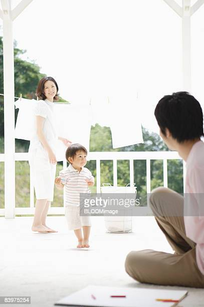 Mother hanging laundry to dry, father looking at baby walking toward him