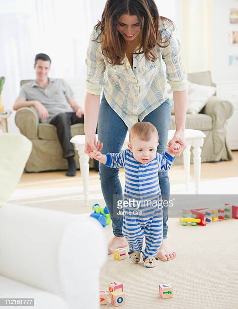 Mother helping baby boy walk, father in background